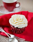 A cupcake decorated with a white chocolate rose