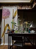 Verschiedene Vasen mit Blumen auf Tisch, im Hintergrund Poster mit Zwiebelblüte-Motiv