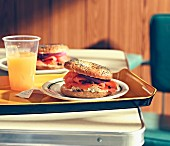 A poppy seed bagel with salmon and cream cheese served with orange juice on a tray in a restaurant