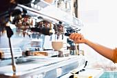 A barista at the espresso machine in a restaurant