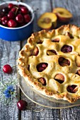 Cherry pie with peaches and a decorative pastry topping