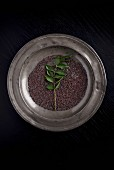 Mustard seeds and fresh curry leaves on a pewter plate (seen from above)