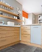 Ecke einer Küchenzeile, Schubladen aus Massivholz, oberhalb Gläser auf Holz Ablagen an hellgrau getönter Wand