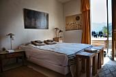 Schlafzimmer im Ethnostil, drei Holzhocker als Ablage am Fußende, Blick durch offene Terrassentür