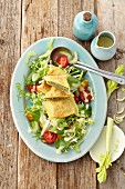 Swabian ravioli on a salad with colourful tomatoes