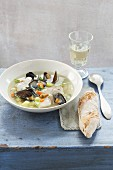 Fish soup with mussels served with baguette and white wine