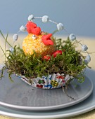 Coconut cockerel in Easter nest made of moss