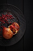 A halved pomegranate on a black plate (seen from above)