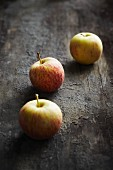 Three apples on a dark surface