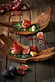 Appetisers with figs, pomegranate seeds, ham and cheese served on pieces of bark