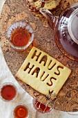 Teatime mit Teekanne, Tee in Gläsern & Keks mit Schriftzug Haus