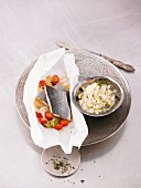Wolf fish in parchment paper with herb tomatoes and courgette risotto