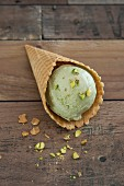 A scoop of pistachio mascarpone ice cream in a cone