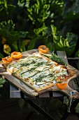 Courgette unleavened bread with goat's cream cheese, apricots and rosemary in front of a courgette bed