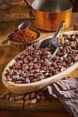 Eine Schale mit Kakaobohnen und Schaufel, Kakaopulver und Kupfertopf