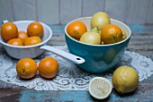 Oranges and lemons in a blue porcelain bowl and oranges in a white enamel colander