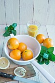 Oranges in an enamel colander, fresh mint, a glass of orange juice and sliced lemons on a board
