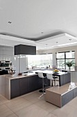 Multifunktionale Küche, Frühstückstheke mit Barhockern, davor angebautes Lowboard, unter abgehängtem Deckenfeld mit Pendelleuchten, in Designerküche