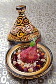 Beetroot chicken with grapes and grain in a tagine