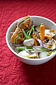Colourful farfalle pasta with baby vegetables
