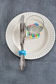 Silver cutlery and a glass decorated with rubber bands on a plate