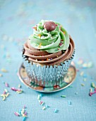 A cupcake with chocolate and lime frosting decorated with chocolate beans and sugar sprinkles