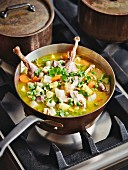 Chicken stew in a copper pan on a stove