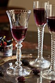 Mulberry liqueur in three stemmed glasses on a tray