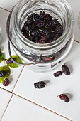 Fresh mulberries in a preserving jar on white tiles