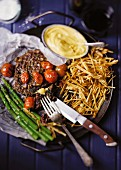 Beefsteak with Bearnaise sauce, green asparagus and potatoes straw