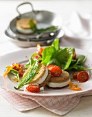 Spinach salad with cherry tomatoes, goats cheese and fried wild garlic
