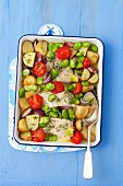 Baked cod with potatoes, broad beans, garlic, onions and tomatoes