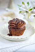 A chocolate cupcake with a fudge topping and sugar