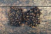 Trester von ausgepressten getrockneten Oliven mit Kernen auf Holz (von der Ölgewinnung)