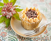 A cupcake with orange cream and chocolate chunks