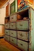 Rustikaler Schubladenschrank mit abblätternder Farbe, darauf Vintage Metallboxen