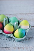 Brightly striped Easter eggs in china egg box