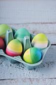 Bunt gestreifte Ostereier im Porzellan-Eierbehälter