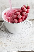 Creamy redcurrant ice cream in a white cup with a frozen sprig of redcurrants