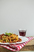 Courgette spaghetti with vegan bolognese and a glass of red wine