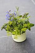 Dill flowers, mint, borrage flowers, savory, rosemary and lemon balm in a yellow enamel mug
