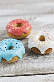 Min doughnuts with pink, blue and white icing and colourful sugar pearls