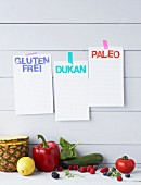 Fruit and vegetables against a wooden wall hung with diet notes