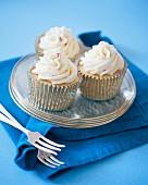 Cupcakes mit weisser Schokoladencreme und Zuckerstreusel