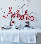 Festive buffet decorated with bare branch and crocheted wire lettering reading 'hohoho'