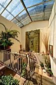 Sonnenbeschienenes Treppenhaus mit Glasdach, auf Boden und Ablagen Blumentöpfe in mediterranem Ambiente