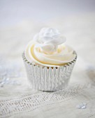 A cupcake decorated with a white sugar rose