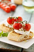 Bruschetta topped with green tapenade, goat's cheese and cherry tomatoes