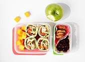 Wraps, fruit and biscuits in a lunch box