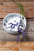 Lavender flowers in a bowl on a wooden surface